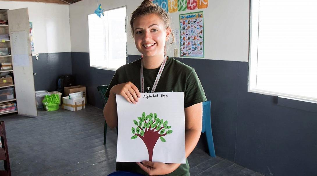 Voluntaria de educación en Belice muestra un ejercicio del abecedario de una estudiante.